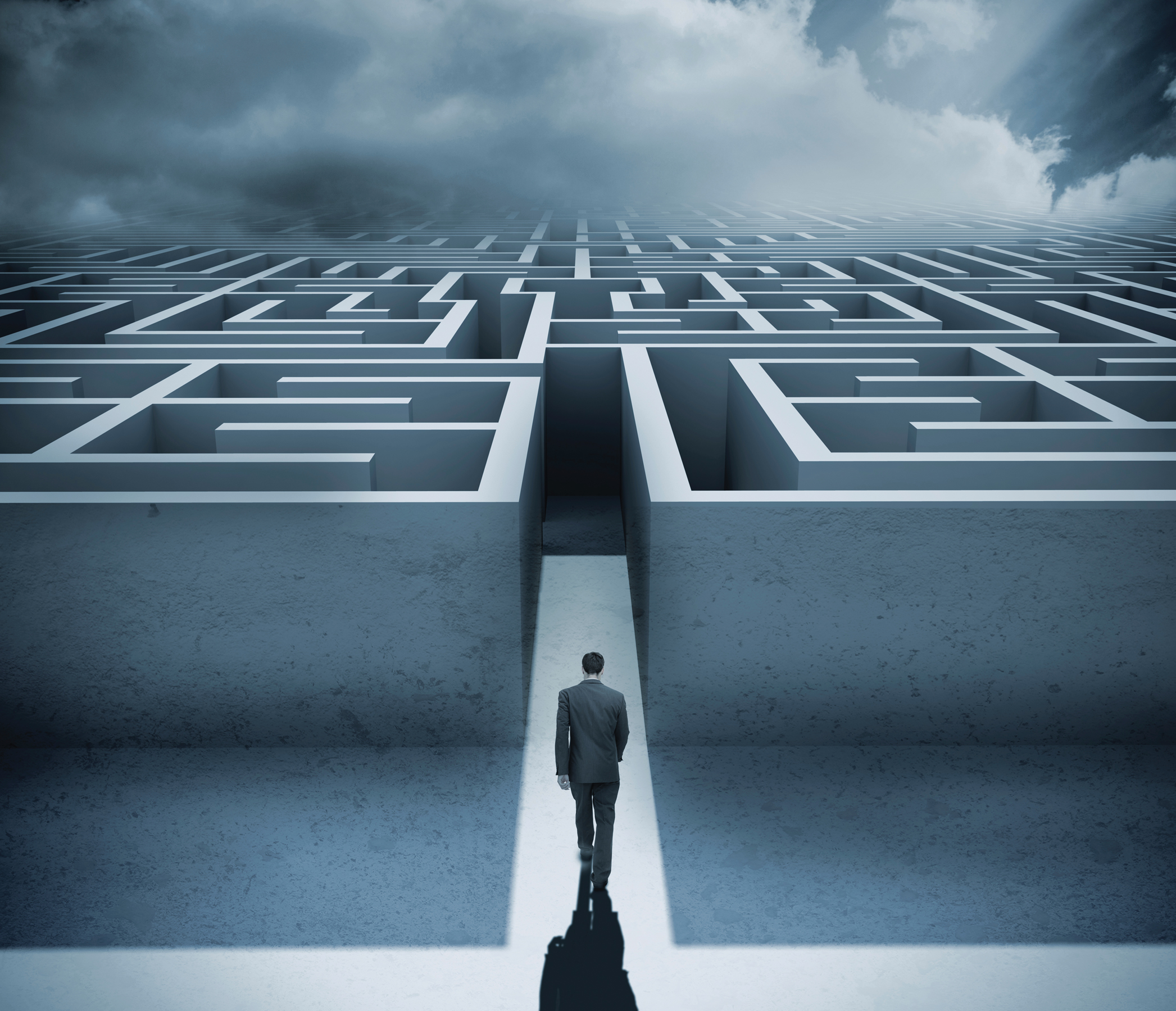 Businessman getting in a maze with dark cloudy sky on the background